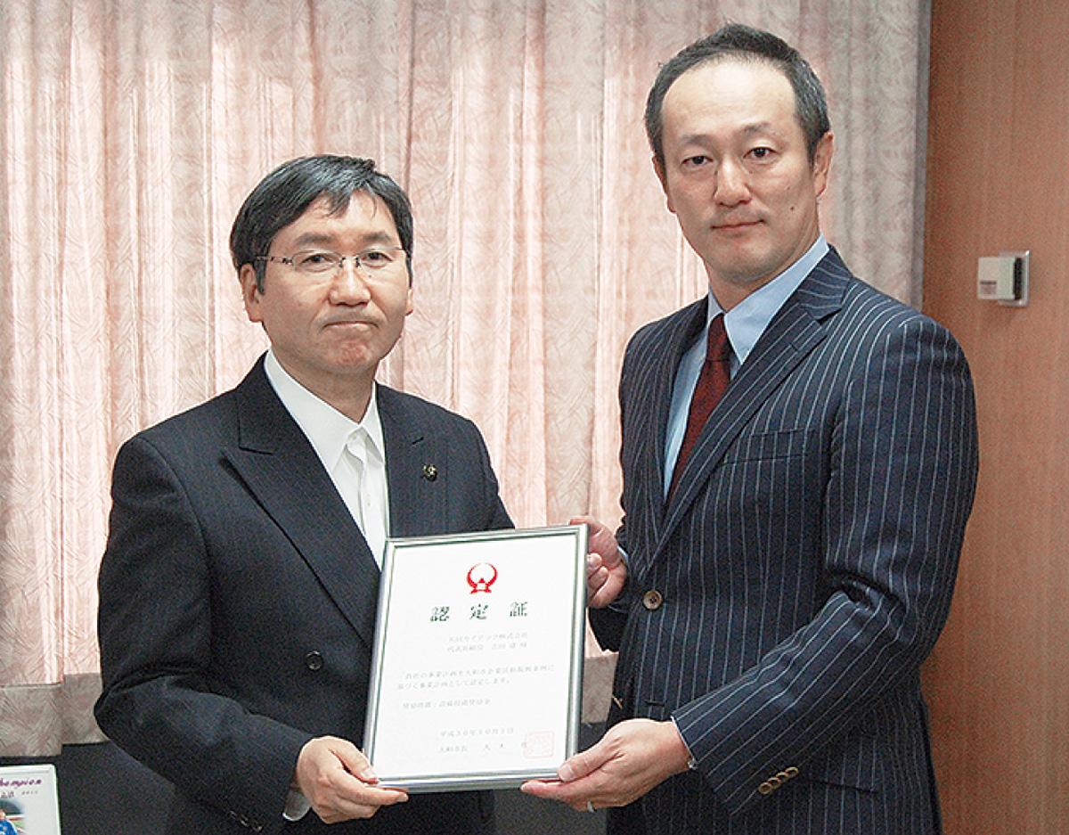 大木哲市長(左)から認定証を受け取る吉田建社長