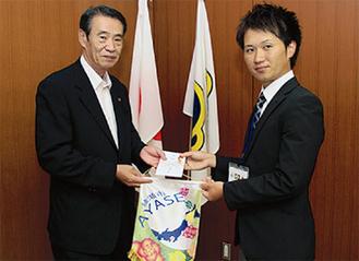 笠間市長から市のバナーなどを受け取る寺薗さん(右)