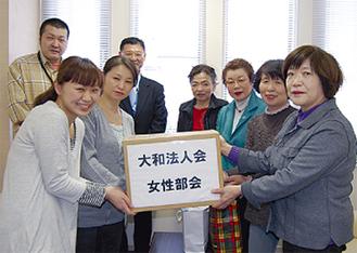 目録を手渡す女性部会のメンバー(右)