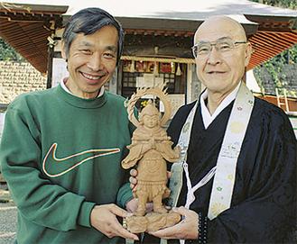 木像を手渡す石井さん(左)