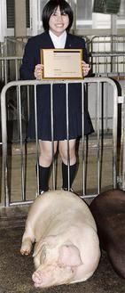 「ちゅのとん」の豚舎で盾を手にする宮澤さん