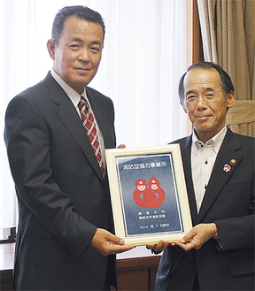 表示証を受け取る木内代表取締役(左)