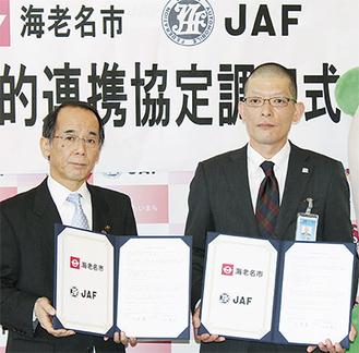調印書を持つ内野市長と行天JAF神奈川支部事務所長