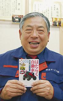 書籍を手にする八木社長