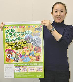 今年のカレンダーを手にする市職員