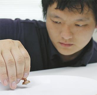 コマ回しに全神経を注ぐ製作者の加賀崎さん