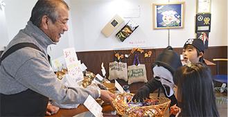 仮装した子どもにお菓子を渡す