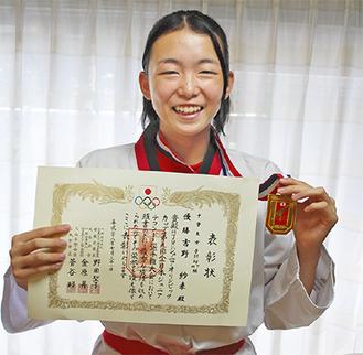 賞状とメダルを手にする吉野さん
