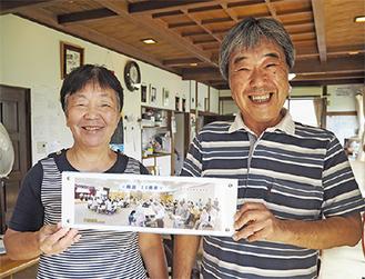 10周年記念祭の写真を手に微笑む鹿島理事長(右)と鶴川さん(左)