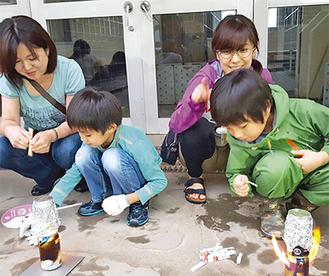 空き缶を使って「炊飯体験」をする親子