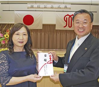 目録を渡す佐藤会長(左)と新井学校長