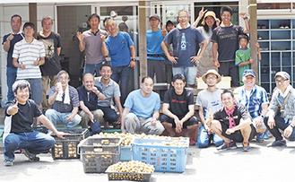 収穫したジャガイモを前に笑顔のメンバーたち