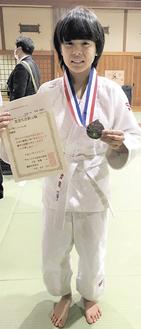 賞状とメダルを手に笑顔の平林さん