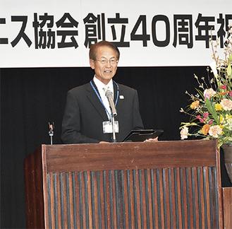 記念式典で挨拶する塩脇会長