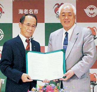 協定書を取り交わす内野市長と駒井町長(右)