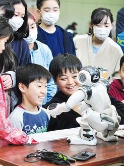 しゃべったり踊ったりするヒト型のコミュニケーションロボットに夢中になる児童
