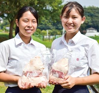 パック詰めされたアヒル肉を持つ養鶏部の岩見摘希さん(左)と足達芽以さん(右)