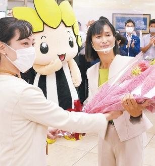 職員から花束を受け取る佐藤市長(右)