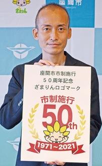 ロゴを持つ飯田さん