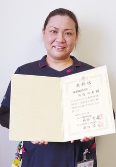 表彰状を持つ小島仁美さん