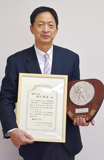 表彰状と盾を手にする金沢哲男前監督
