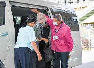 接種会場に到着してバスから降り、付き添いの太田さんにお礼の言葉をかける利用者=綾瀬市保健福祉プラザ