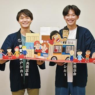受賞式で使った飛び出す絵本を手に持つ増渕さん(左)と中峰さん(右)