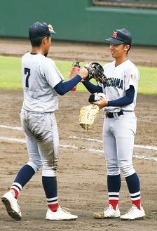金井選手に投手用グローブを届ける山田投手(右)=サーティーフォー保土ケ谷球場