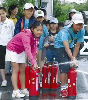 使い慣れない水消火器に挑戦する参加者
