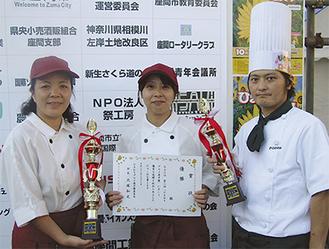 トロフィーを手にするポエムの安西賢一さん(右)と、パン工房どりーむの井上幸子さん(中央)と小澤佳代さん