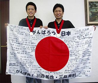 応援の横断幕を手に笑顔の三品さん(左)と川辺さん