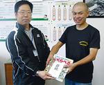 加藤会長(右)から尾崎校長へ本が手渡された