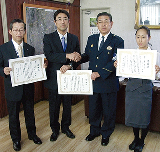 花本署長(右から2番目)と握手する三輪支店長。窓口で犯罪を防いだ井出さん(左)と井上さん(右)
