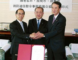 調印式で手を組む遠藤市長(中央)、内野海老名市長(左)、笠間綾瀬市長