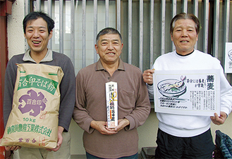 座間神社のお神札(ふだ)を手にする瀬川代表(中央)と、高波義雄さん(右)。畔上秀雄さん(左)が持つのは、神社でお祓いを受けたそば粉