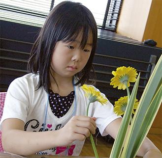 花を前に真剣な表情で取り組む児童