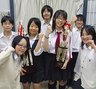 部員に囲まれて、トロフィーを持つチーフディレクターの鈴木さん(右)と則次さん