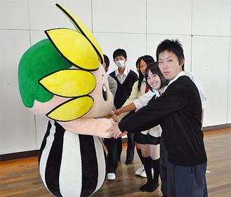 竹尻前会長(写真手前)と握手を交わすざまりん