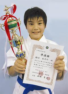 賞状とトロフィーを手に笑顔の佐竹君