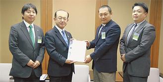 鈴野理事長(中央右)が遠藤市長に手渡した