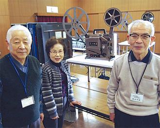 図書館から借りた16㎜映写機を囲む織原会長(右)、宮地怜子さん(中央)、佐藤雅彦さん