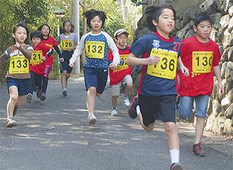下り坂を勢い良く走り抜ける子どもランナー