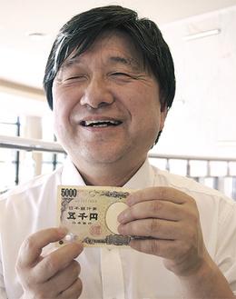ホログラムを指さす鈴木副会長※手にしているのは改良前の5千円札