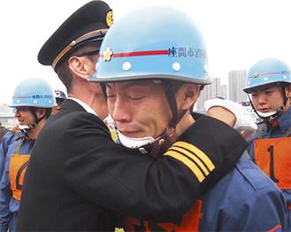 涙を見せ、鈴木団長(左)と抱き合う高波さん