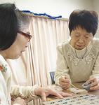 栗原ホームの利用者を指導する菊池さん(右)