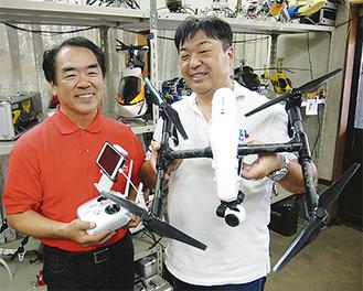 ドローンのリモコンを持つ吉田さん(左)。依田さんが手にしているのが、大会で使った実機