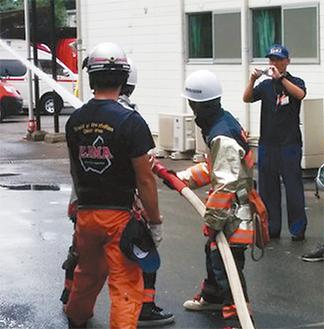 消防士と同じ装備を着用して、放水に挑戦する参加者