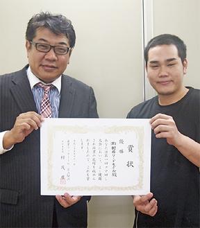 賞状を手に喜ぶ迎代表(左)と製作に携わった濱谷一輝さん