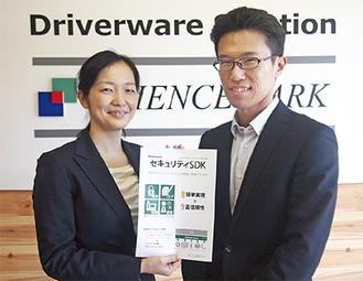製品のパンフレットを手にする井上さん(左)と永尾さん