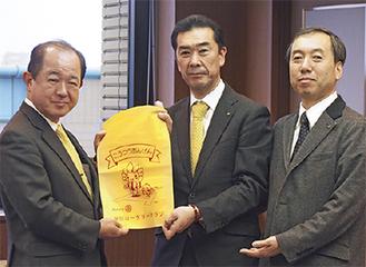 同クラブ細川会長(中央)と片野光庸さん(右)が、遠藤市長にカバーを届けた